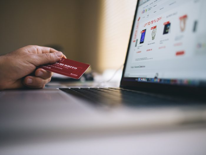Person holding a credit card and preparing to shop online.