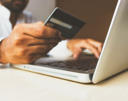 Man using a credit card to purchase something online.